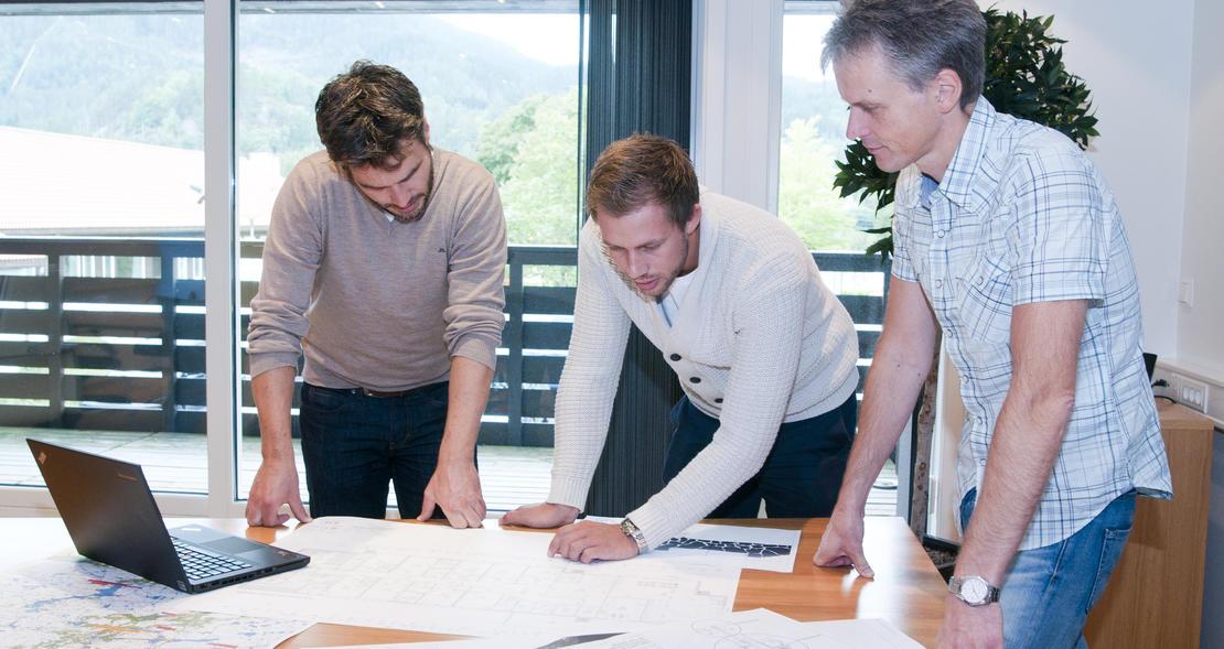 Tre menn ser på dokumenter