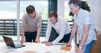 Tre menn ser på arbeidstegninger