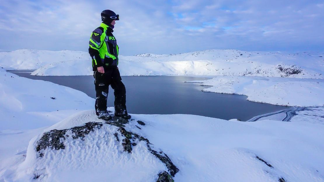 Mann ser ut over snødekte fjell
