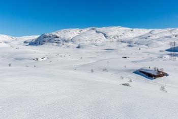 Snødekket fjellandskap med kraftlinjer