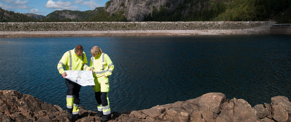 To personer ser på et kart ved en dam