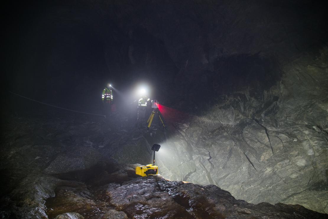 Menn med laser og lommelykt i tunnel